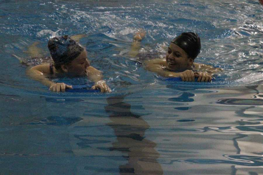 FHC teammates swim together in practice. They used kick boards to practice their strokes.
