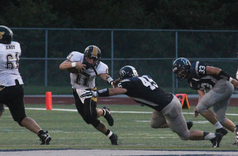 East quarterback Shane Barrett scrambles away from pressure on Friday during East's win over the football team.