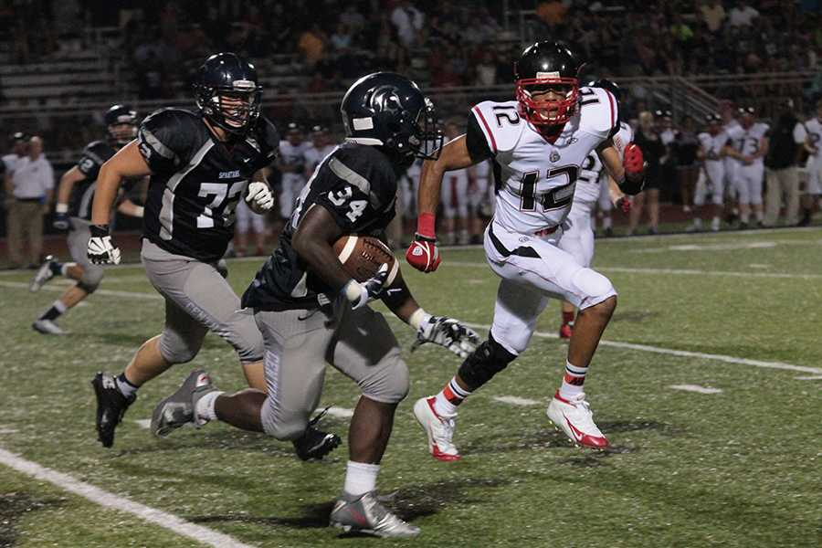 Running back Jordan Cooper tries to escape the tackler as the football teams falls to Fort Zumwalt South.