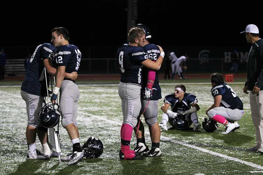 Senior football players embrace each other after their loss to rival Francis Howell on senior night last Friday, Oct. 3.