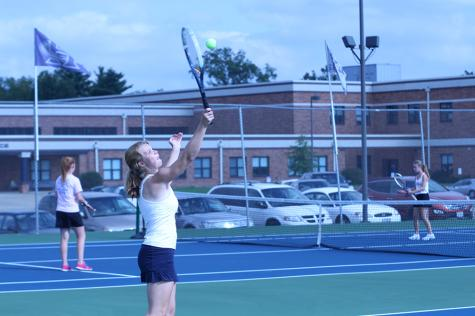 Senior Elise Thomas hits the tennis ball, aiming for victory.