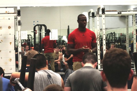 Alumnus Pierre Desir visits with the football players at their before school weight lifting session last Friday.