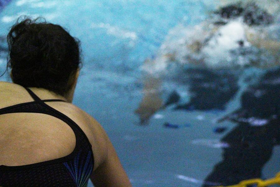 A girl's swim team member encourages her teammate to finish the race strong.  With this attitude, the team believes they can take home a win at districts.