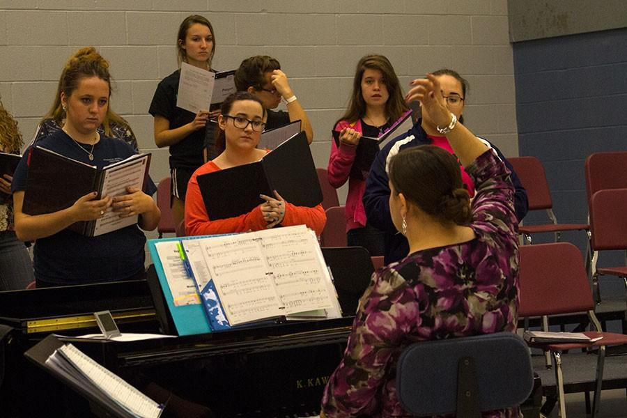 Choir director Elisabeth Baird gestures to the members of her third hour Treble Choir class. The choirs are making plans to make themselves  visible  this year, including singing during passing periods or pep assemblies.