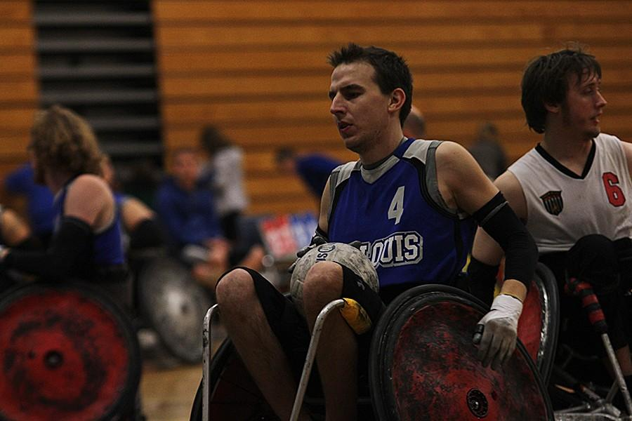 David Miles carries the ball towards the opposite teams goal line during the Crazy 8 wheelchair Rugby tournament. The tournament was held in the gymnasium here at FHC with the help of volunteers, family, and friends.