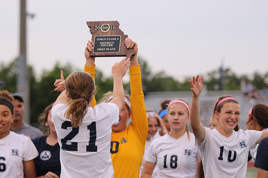 Senior Emma Farley raises the Class 4, District 6 trophy toward her teammates after the girls soccer team defeated Fort Zumwalt West on Thursday, 2-1.