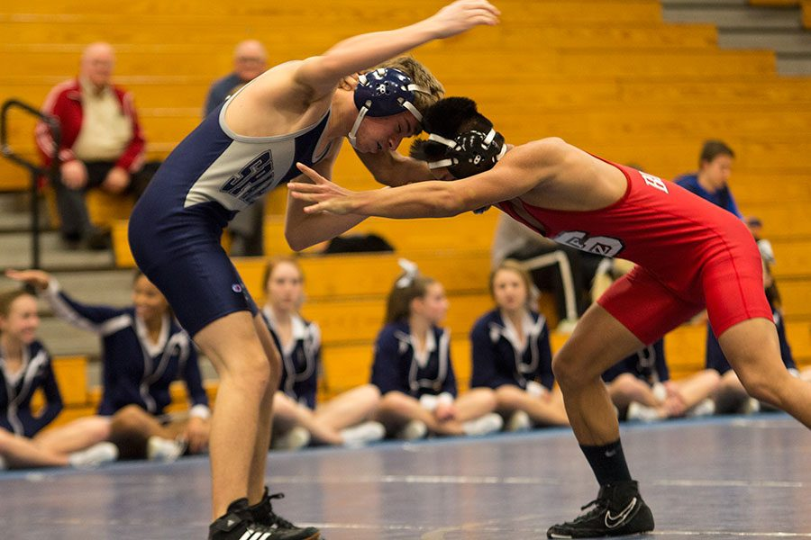 Sophomore Nick Mallon evades a locking move from his opponent in his varsity match. The team is laser-focused on another consecutive state title for this year's season.