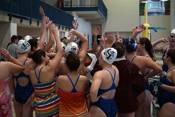 The girls swim team gets pumped up during the first day of the GAC swim and dive meet on Feb. 7. Eight members of the team qualified for the second day of the GAC meet.