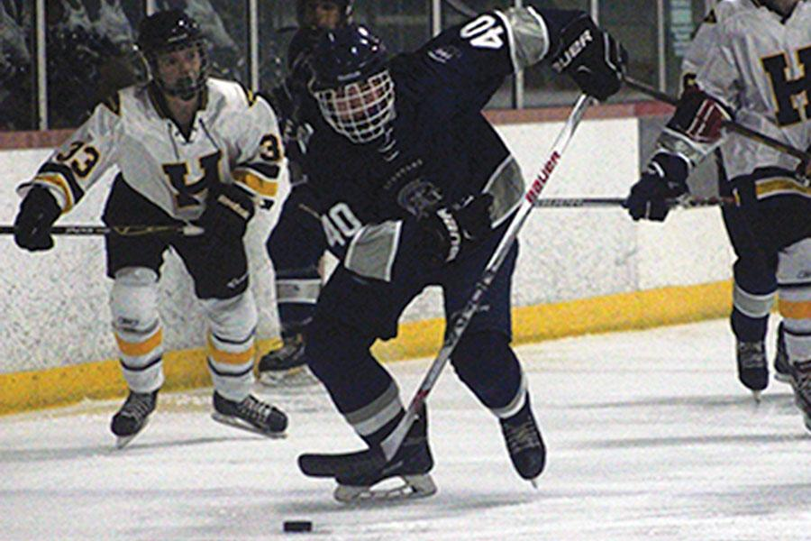 Junior, Corey Moats, breaks free of opponent, Holt High, and skates the puck down the ice. He scored two out of three goals this game, but unfortunately, the team lost in overtime.
