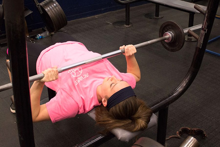 Kaitlyn Chadwick working out sing the bench press,  this will make her stronger in the arms and core