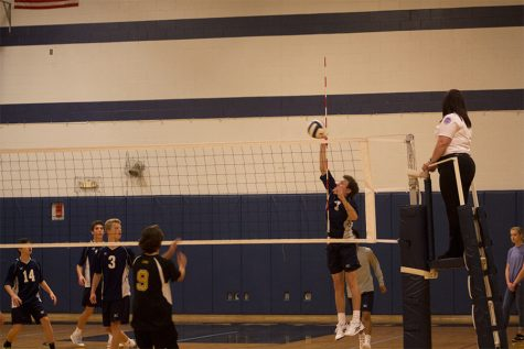 Dylan Stover tapping the ball over the net. The freshman team is undefeated with a record of 11-0.