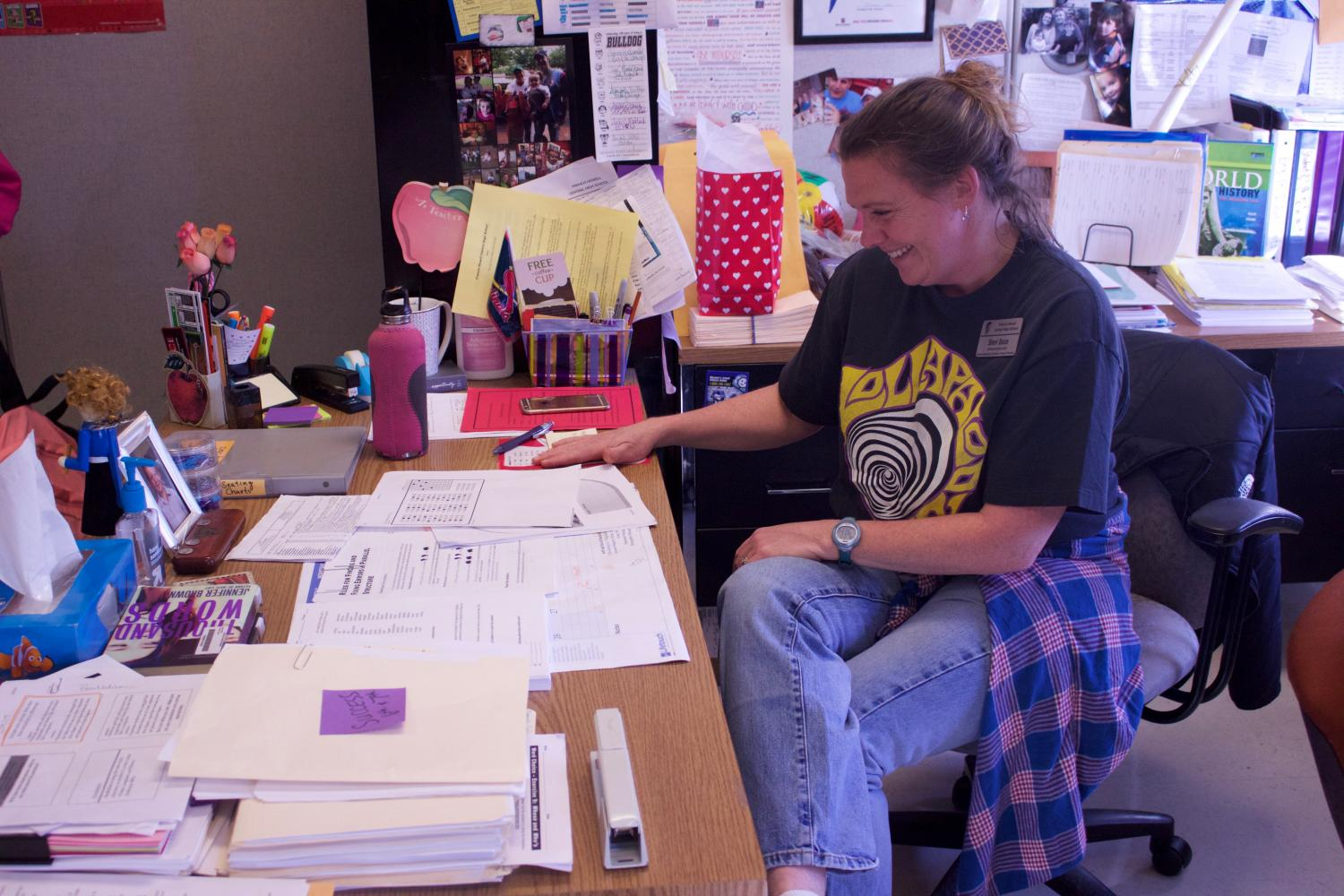 Mrs. Baize grins while getting work done at her desk. She teaches English along with sponsoring the Speech and Debate club.