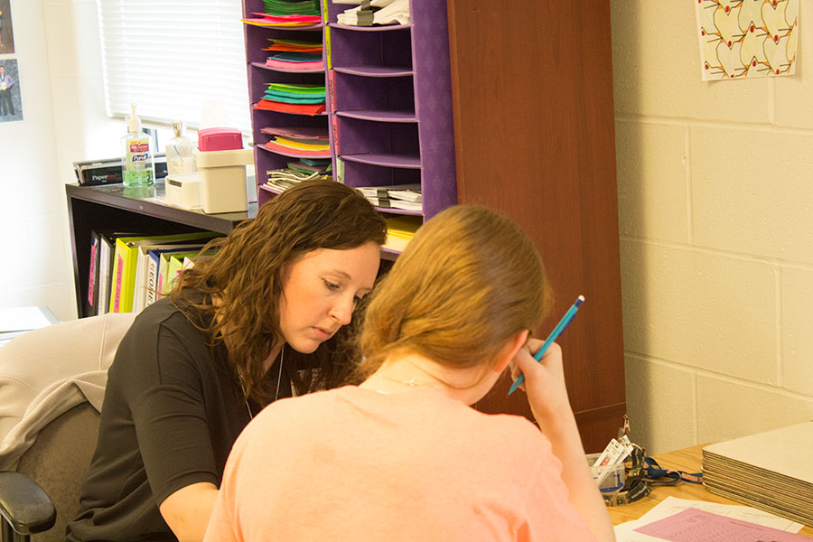 Mrs. Morrow intently helps a student. Mrs. Morrow teaches geometry.