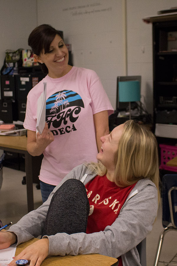 Mrs. Schafer laughs with a student during class. She teaches both Economics and Marketing.