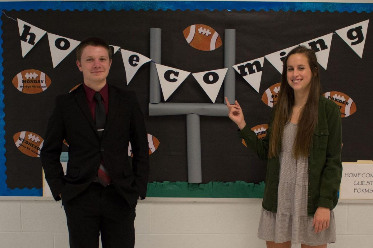 Senior Aly Janis and Junior Gabe Prather stand with FHC homecoming advertisement sign