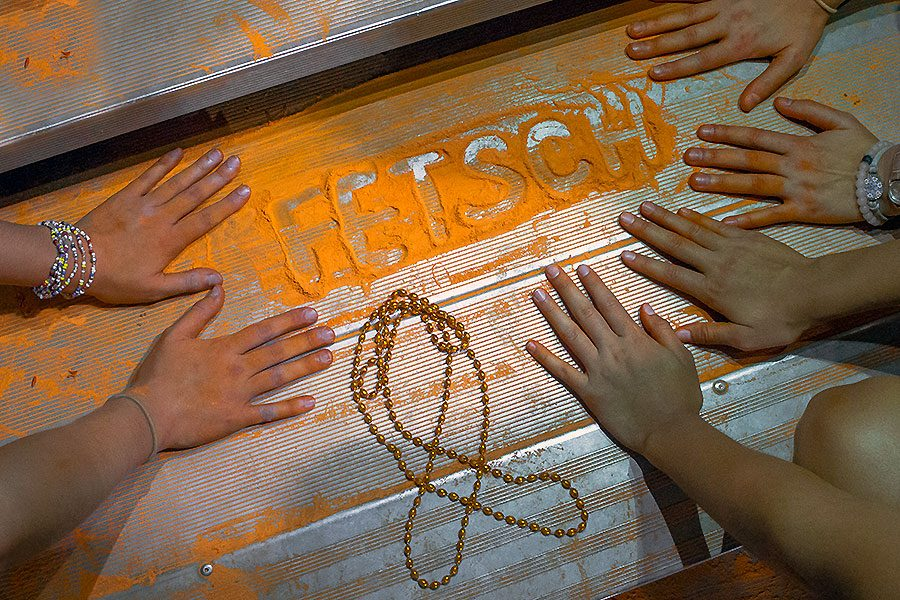 After orange flour was tossed in the air at the Sept. 15 football game against Troy Buchanan, students spelled out Roxanne Fetsch's last name in leftover flour and made a ribbon out of orange beads.