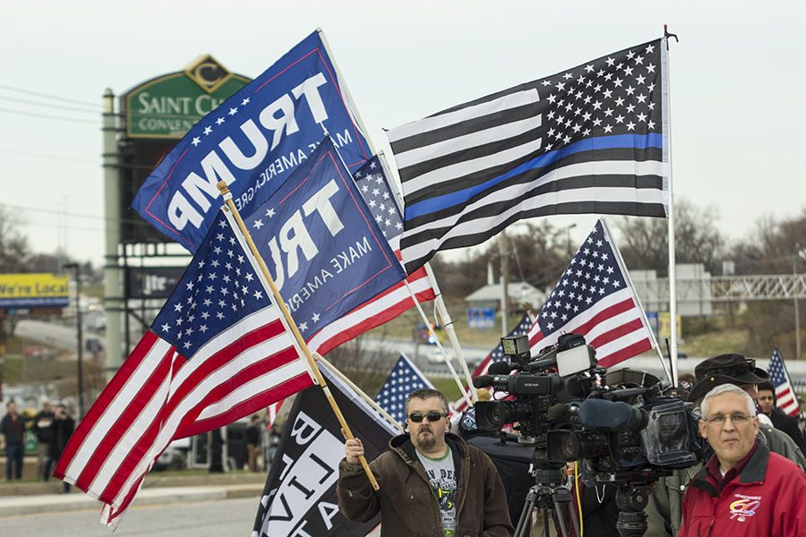 Protesters outside the St. Charles Convention Center wave Trump flags while awaiting his arrival. President Trump traveled to St. Charles to speak about tax cuts.