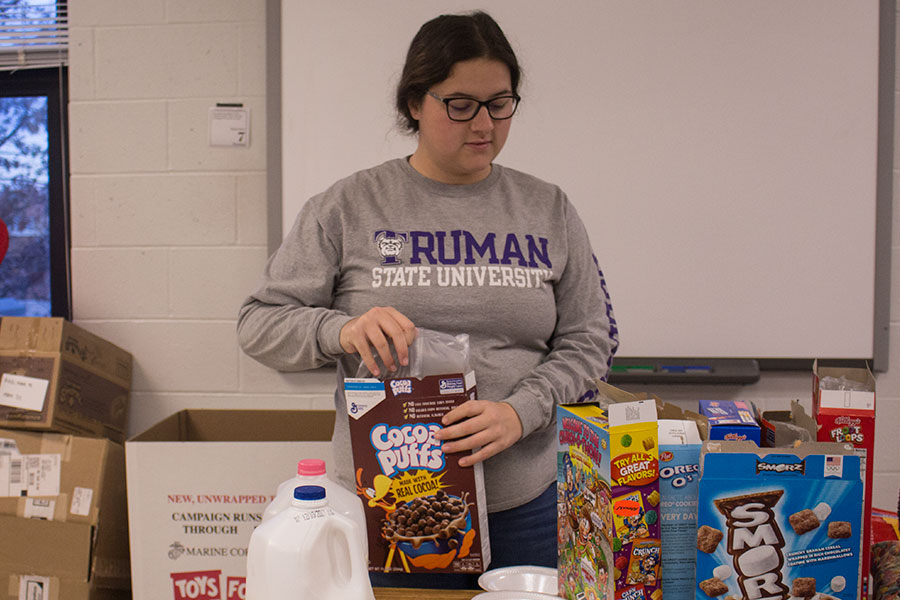 Grace Heisel opens a box of Coco Puffs at Cereal Club. At the meeting, she and other members enjoyed their breakfast together.