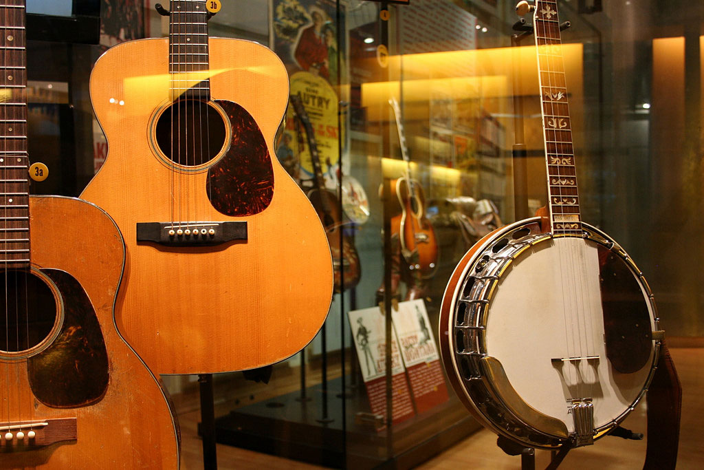 Several acoustic guitars and banjos are on display at the museum of country music in Nashville, Tennessee. Country music tends to be controversial, but is better than its reputation.
