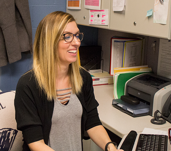 Stacey Galloway sits at her desk and explains aspects of her daily duties.