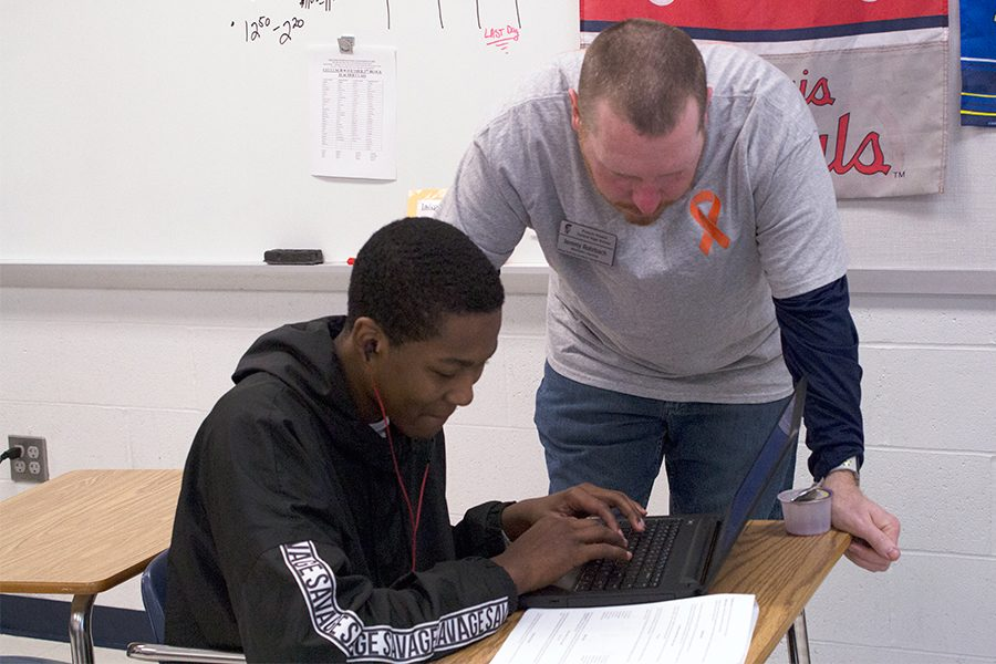 Mr.+Rhorbach+leans+over+a+student+to+help+with+his+assignment.+He+always+does+his+best+to+ensure+his+kids+understand+the+curriculum.+