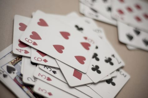 Playing cards, scattered on a surface. Most basic card decks can be used for the games listed in this article.