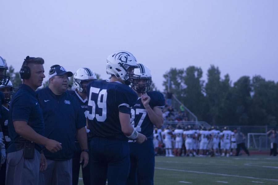 Players and coaches look on as the Spartans play their first game without Coach Todd Bizzell. The Spartans lost 43-28.