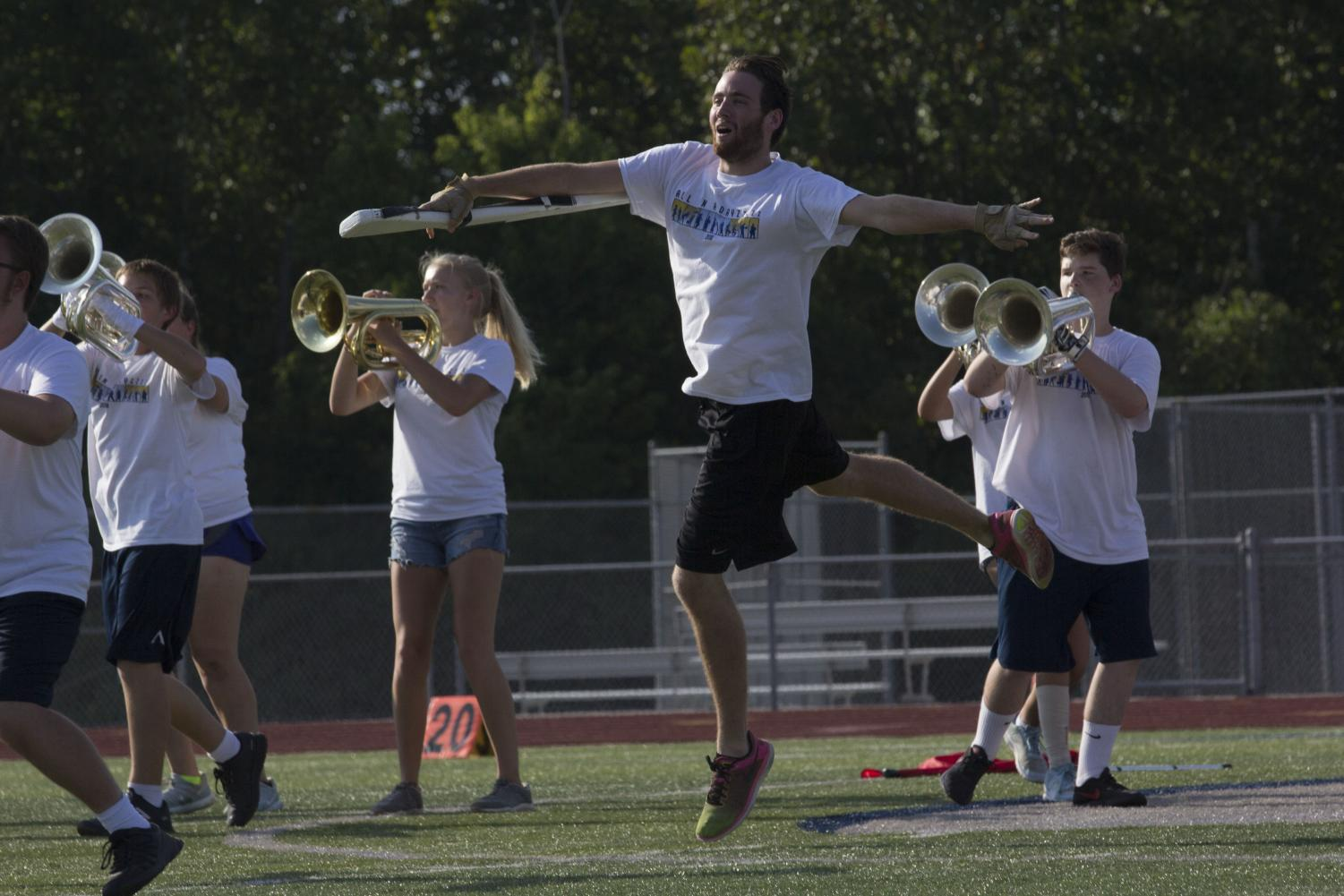 Senior Color Guard member Michael Foley leaps into their air. The routine for