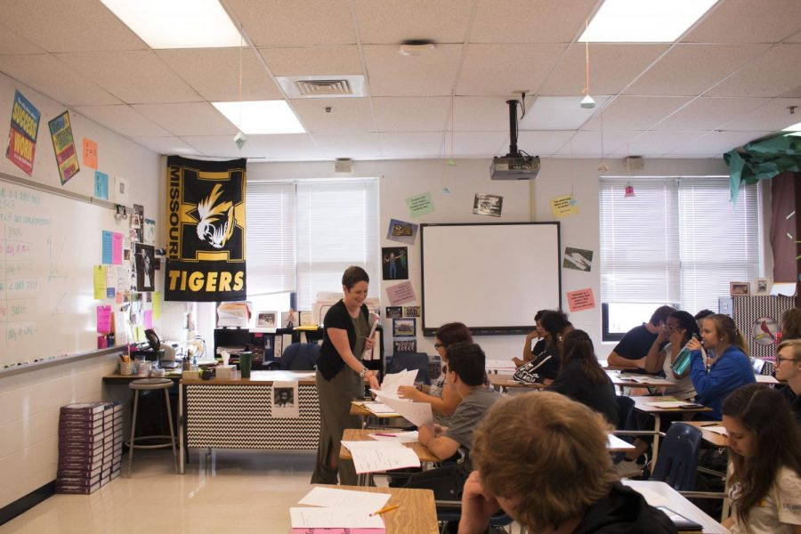 Mrs. Fetsch smiles as she passes out papers to students after accidentally allowing them to start an assignment meant for another day. Fetsch finds entertainment in every aspect of her job.