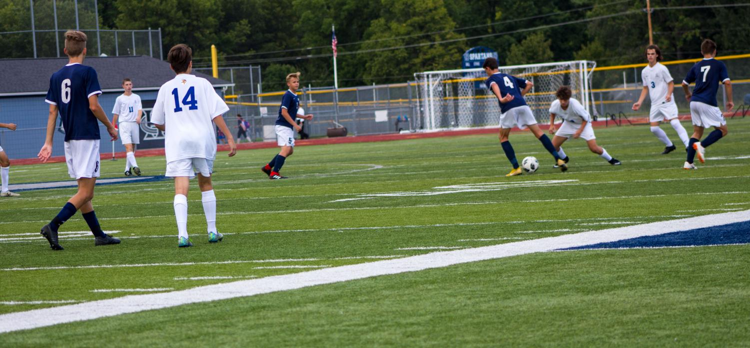 Junior Luke Hantack prepares to pass the ball to his teammate as Howell player advances on him.