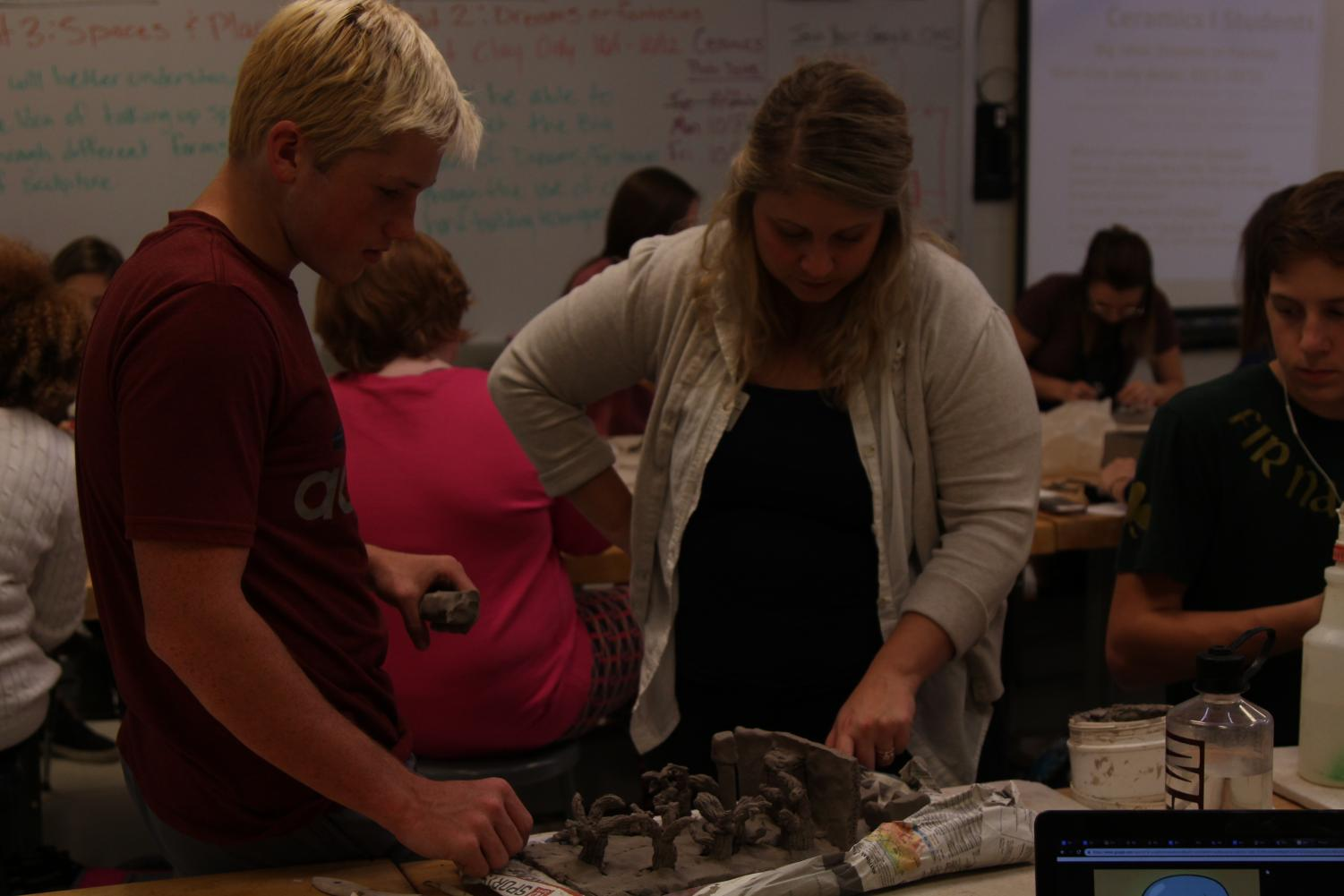 CREATE: Mrs.Sprick helps a student during her first hour ceramic class.