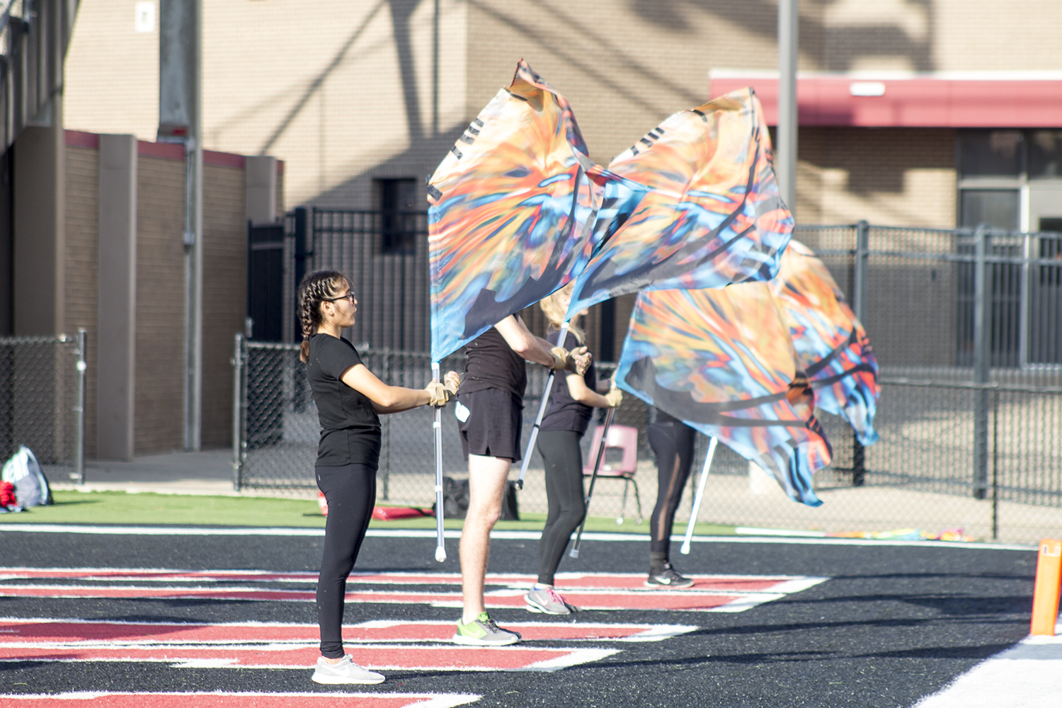 The color guard practices its routine on a field in Tulsa, Okla.
