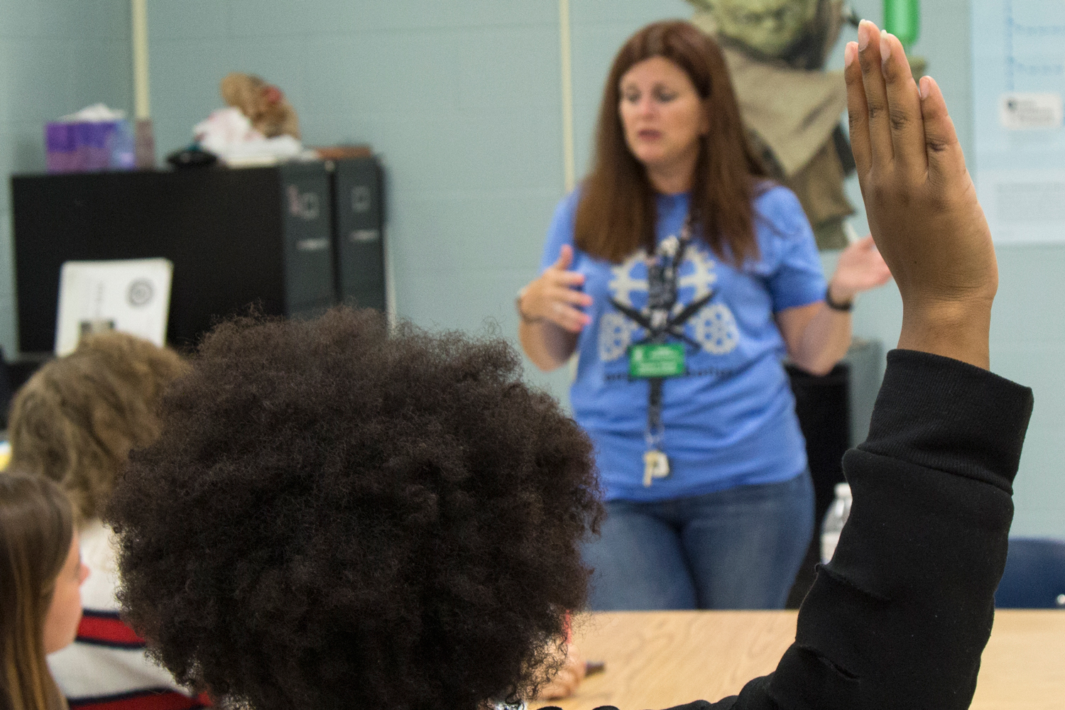 Lizzie Dailey-LeFlore raises her hand to ask teacher, Ms. Flood, a question about her independent oratory project.