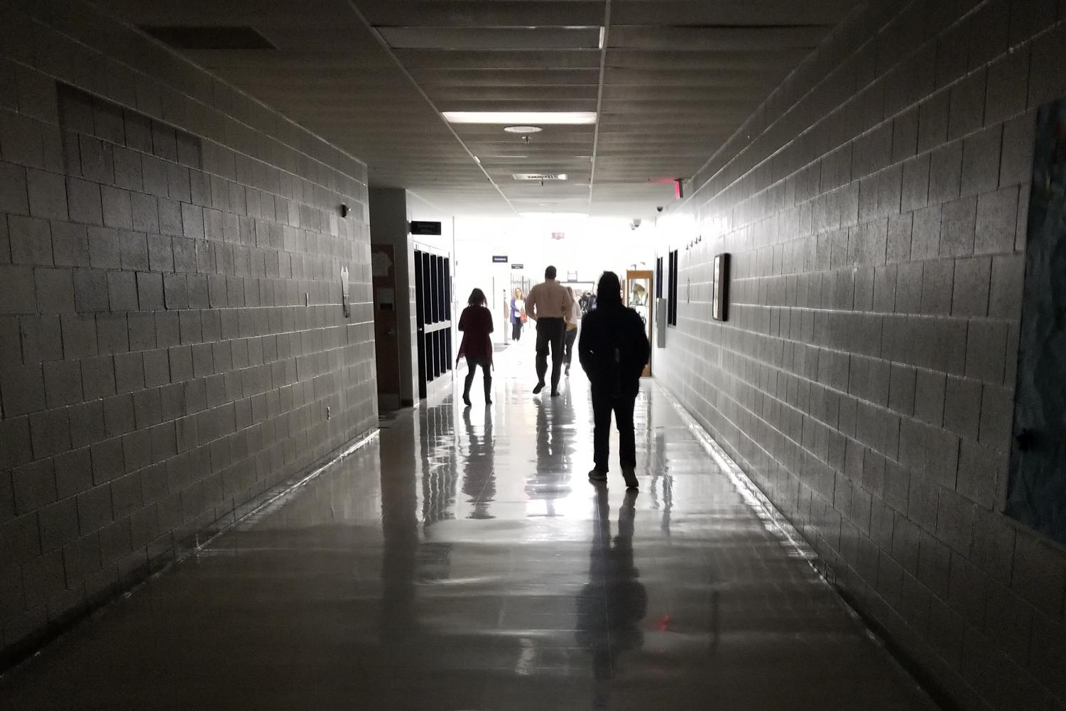Students and staff walk towards the lit wing of the school. The power outage had only impacted the classroom side of the school, so students were guided to the gym to wait for instructions.