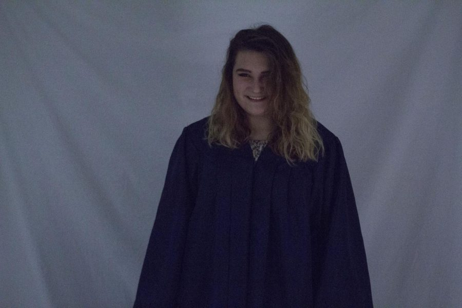 Senior Whitney Klein laughs along with friends in her graduation gown. Taken on her last day of high school, the image contains an array of emotions.