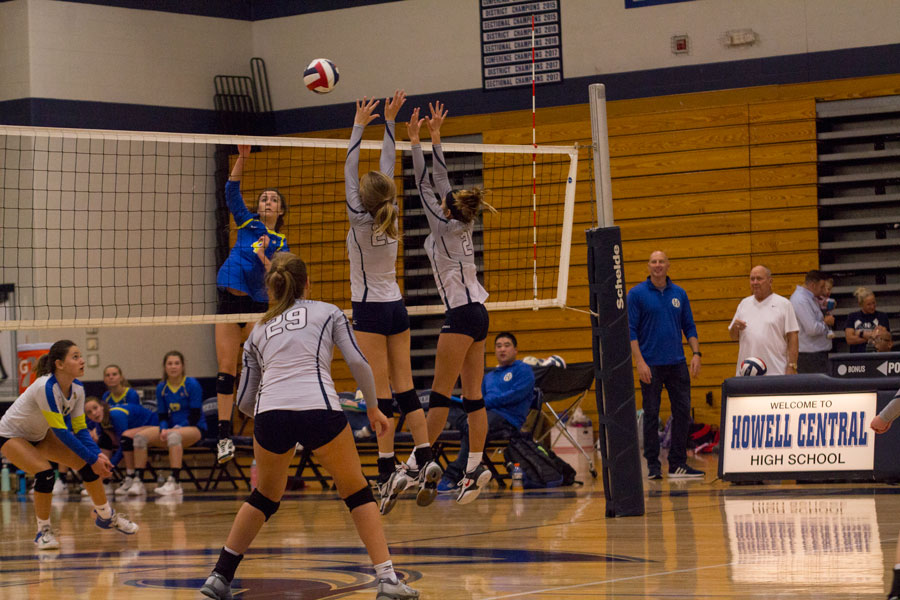 Two Spartan volleyball players block the ball.