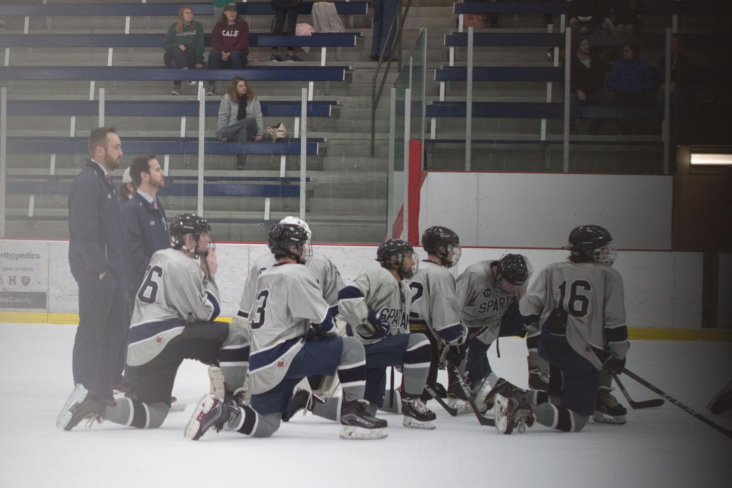 The Spartan ice hockey takes a knee as a huddled mass. The team utilizes this time to discuss the name with one another.
