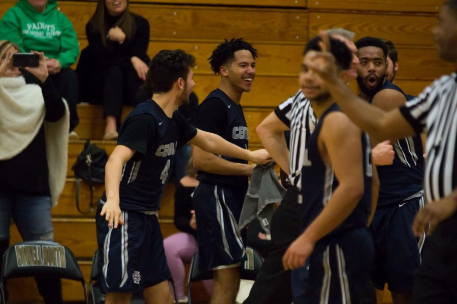 The varsity boys basketball team congratulate each other as they score at their game. The team secured a win against Howell North with a score of 61-48.