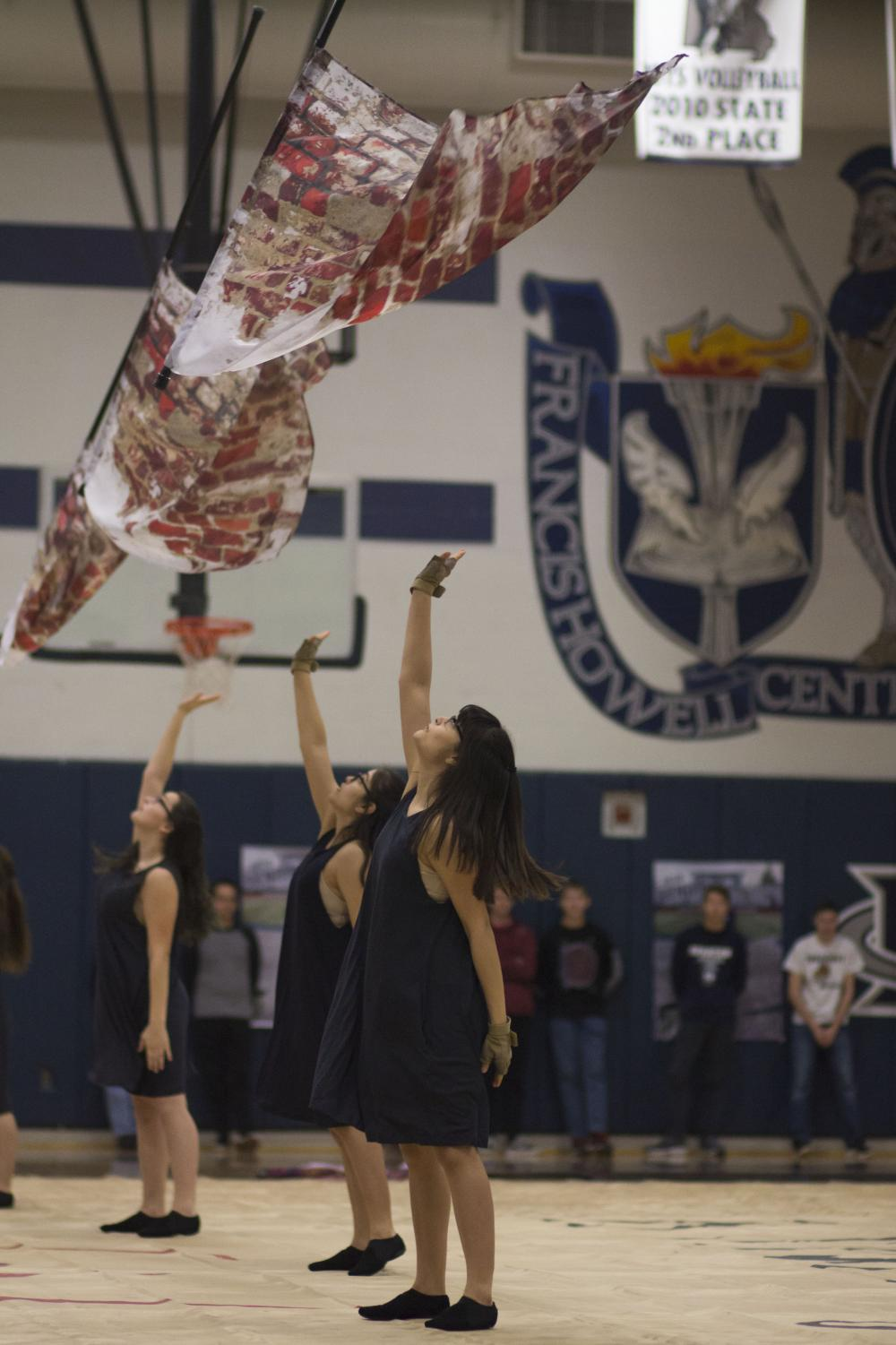 Marie Cook, Elyssa Herrera and Evelyn Herrera perform at the Pink Out Pep Rally. The seem to be spinning their flags in time.