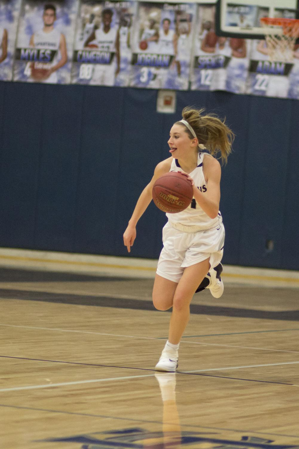 Gracie Stugart drives down the court, tongue sticking out, displaying her passion and love for the game. her enthusiasm is clear as she looks for one of her teammates to pass the ball to.