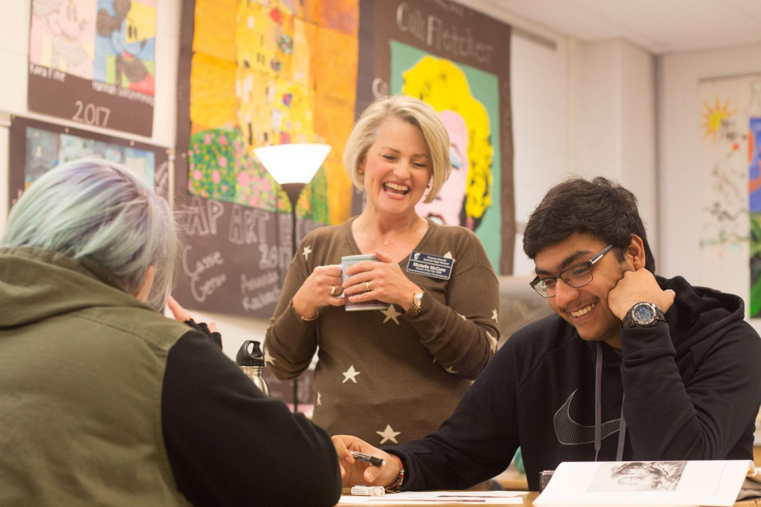 Senior Rishith Mishra laughs along with Michelle McCune during AP Art History. Mishra talks Mrs. McCune about his life because he knows that she will listen and help him problem-solve.