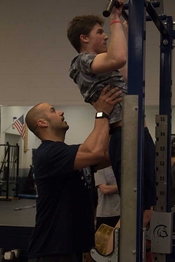 Coach Radigan assists a student with pull-ups.