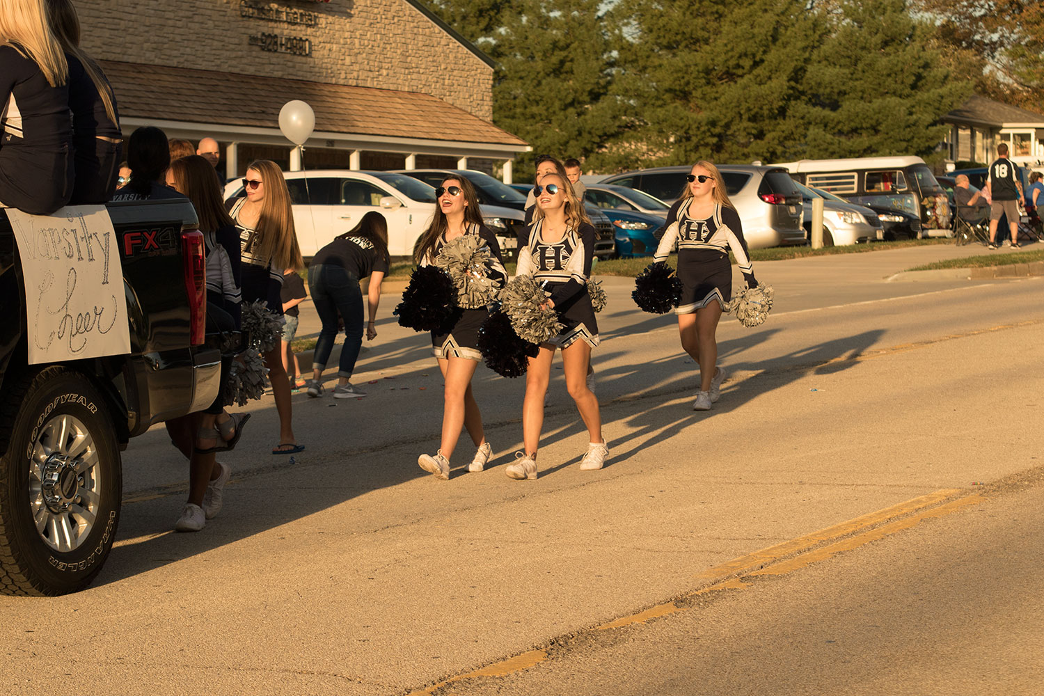 The varsity cheerleads walk at the homecoming parade showing their school spirit as they smile at children
