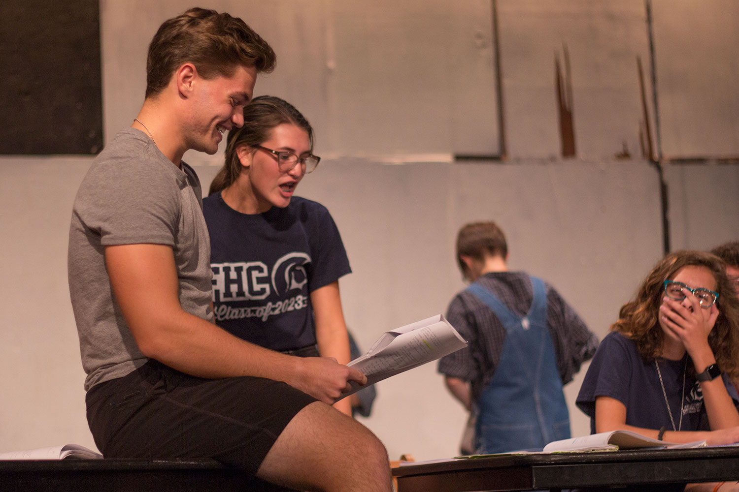 Kaylee Wright laughs while running through a section of the script with senior Sam Cole during rehearsals for