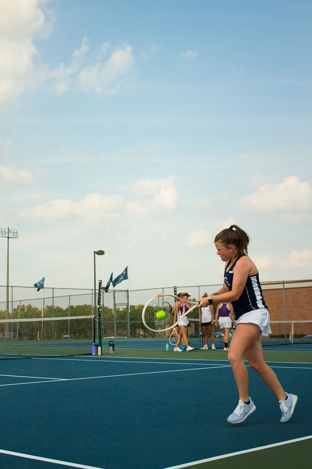 """In the middle of returning the tennis ball to the other side of the net. You can see the dedication on Natalie Hall's face. She says: """"I thought that the Teacher's appreciation day was a good experience and a good environment for the match""""."""
