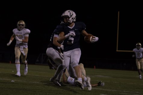 Kannon Cissell evading a defender while running along the sideline.