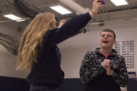 Junior Dylan Waters laughs and claps as he and Sophomore Zoe Grumich play with bean bags. The two students generally work together during third period. The bean bags and other toys are things they are allowed to play with during their Adaptive PE Class, a class that has been on the books as been available to students but hasn't had the enrollment or equipment to support it.