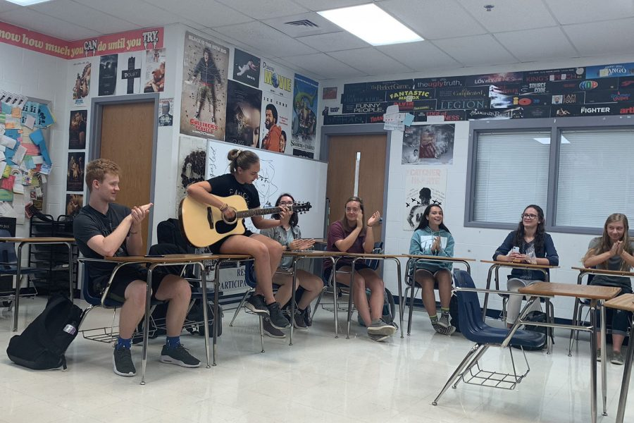 JAM SESSION: Alli Rush plays a song on her guitar for her English class, much to her classmates' delight. Rush brought her guitar to school for extra credit on a Spanish assignment and played for her other classes as well.