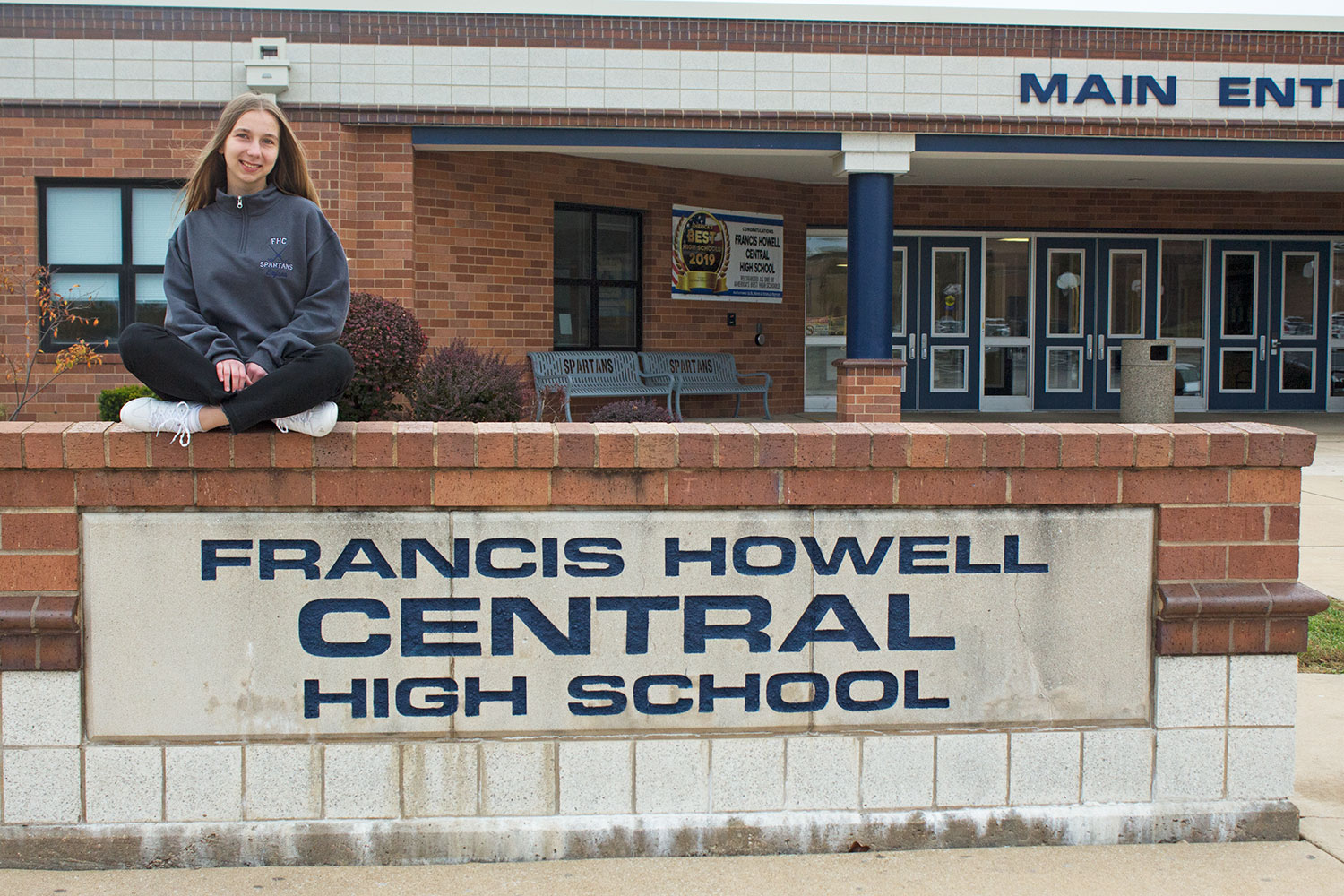 Bojana Kuzmanoska poses in front of Francis Howell Central where she is currently attending high school. The smile on her face displays how happy she is to be in America.