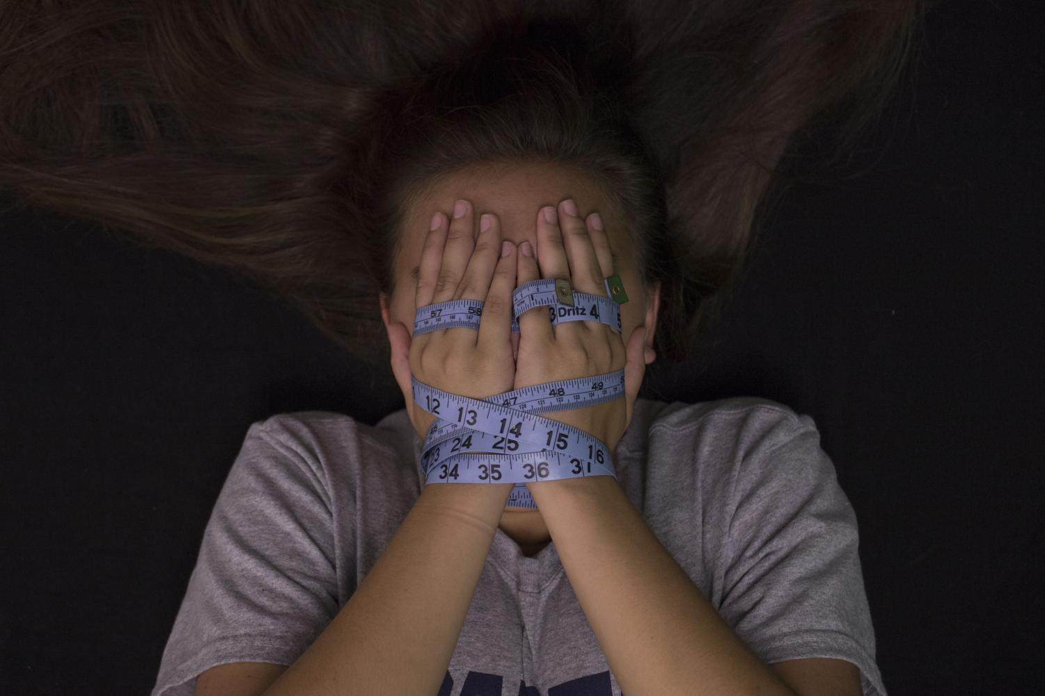 A girl's hands are bound in a tape measure as she covers her face. Eating disorders often make individuals feel trapped within their own bodies.